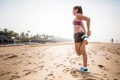 Бегун женщины протягивая ноги muscles на пляже на восходе солнца Стоковое Изображение RF