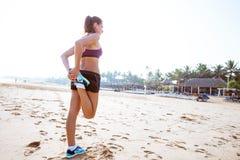Бегун женщины протягивая ноги muscles на пляже на восходе солнца Стоковое Фото