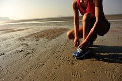 Бегун женщины связывая шнурок перед бежать на пляже Стоковое фото RF