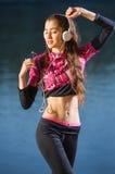 Бегун женщины с наушниками наслаждаясь музыкой outdoors Стоковая Фотография RF
