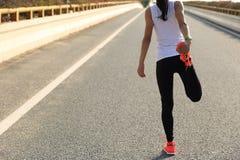 Бегун женщины фитнеса протягивая ноги перед бегом стоковое фото rf