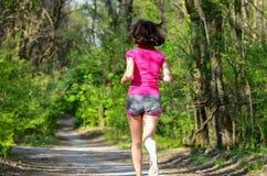Бегун женщины jogging outdoors в лесе Стоковые Фотографии RF