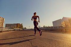 Бегун женщины jogs на мосте в городе Стоковое Изображение RF