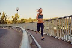 Бегун женщины jogs на мосте в городе Стоковое Изображение