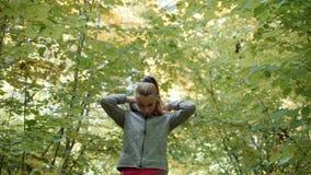Бегун кладет дальше клобук и продолжает к бегу Девушка застегнутая вверх на куртке, положила клобук на ее голову и сток-видео