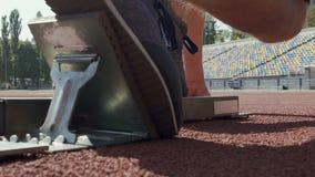 Бегун кладя его ноги на footplates начиная блоков и бегов после команды акции видеоматериалы