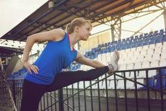 Бегун молодой женщины протягивая ноги перед бегом во время солнечного утра на следе стадиона Женщина бегуна протягивая раньше Стоковые Изображения RF