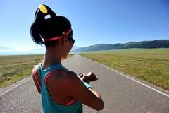 Бегун молодой женщины готовый для того чтобы побежать установленное и смотреть вахта спорт умный Стоковая Фотография RF
