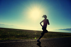 бегун молодой женщины образа жизни бежать на дороге восхода солнца стоковая фотография