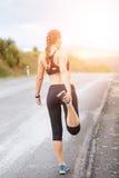 Бегун молодой женщины протягивая ноги перед бегом Стоковое Изображение RF