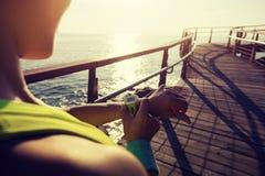 бегун настраивая вахту спорт перед бегом на побережье восхода солнца Стоковое фото RF