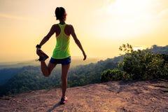 Бегун следа женщины нагревая на утесе верхней части горы Стоковая Фотография