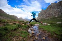 Бегун следа женщины скача над водой потока на горе стоковая фотография