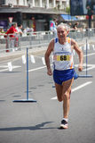 Бегун старика около финишной черты 21-ого,2 апреля Стоковое Изображение