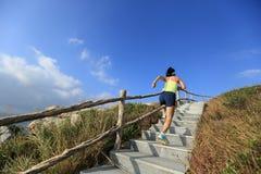 Бегун следа женщины бежать вверх на лестницах горы Стоковое фото RF