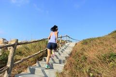 Бегун следа женщины бежать вверх на лестницах горы Стоковые Изображения