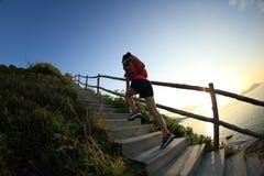 Бегун следа женщины бежать вверх на лестницах горы Стоковая Фотография
