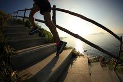 Бегун следа женщины бежать вверх на лестницах горы Стоковые Фото