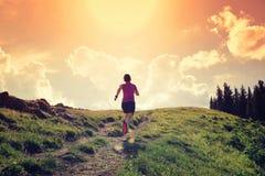 Бегун следа молодой женщины бежать на красивой горной тропе Стоковые Изображения