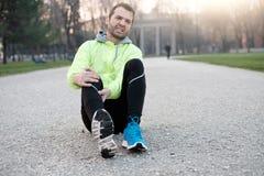 Бегун с раненой лодыжкой пока тренирующ в парке города в col стоковое фото