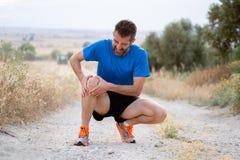 Бегун с ушибом спорта к колену стоковое фото rf