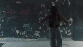 Бег девушки на подземном проходе и слушает к музыке от smartphone Девушка в наушниках и вскользь одеждах видеоматериал