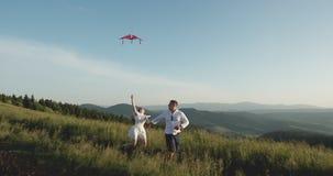 Бег к верхней части холма со змеем летания в руке ( r Бег со змеем летания имеет потеху видеоматериал