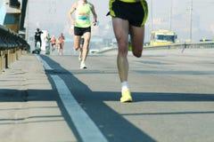 Бег на дороге города Ход марафона в свете утра Бег ног бегуна спортсмена Молодые бегуны бежать на мосте города стоковая фотография rf