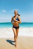 Бег пляжа Женщина фитнеса в бикини бежать в лете Стоковые Изображения