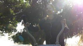 Бег с музыкой, имитатором улицы пользы молодой женщины идущим стоковое фото rf