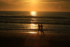 Бежать вдоль пляжа с восходом солнца Стоковые Фото