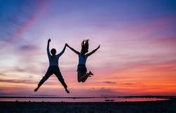 2 бежать и скача девушки на пляже моря захода солнца Рука об руку изображение концепции стоковые изображения