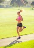 Бежать молодой женщины jogging outdoors Стоковые Фотографии RF