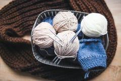 Бежевая, белая и голубая пряжа, вязать иглы в корзине и коричневый шарф Стоковое Изображение RF