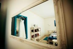 Бежевое платье свадьбы висит на колышке на двери Стоковые Фото