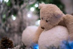 Бежевые снежные комья объятий плюшевого медвежонка при рождественская елка и света запачканные на заднем плане Стоковые Фотографии RF