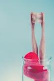 2 бежевых зубоврачебных щетки в стеклянной чашке с красными сердцами на голубой белой предпосылке изолировано фото тонизировало Л Стоковые Фото