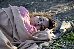 Беженец женщины спать на том основании покрытый с половиком стоковая фотография rf