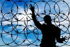 Беженец силуэта мужской и загородка колючей проволоки Стоковые Фото