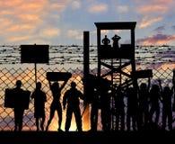 Беженцы силуэта протестуя около границы Стоковые Фото