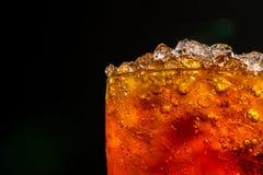 Безалкогольный напиток с задавленными кубами льда в стекле изолированном на задней части темноты Стоковая Фотография