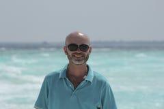 Безволосый средн-постаретый человек на пляже стоковые изображения