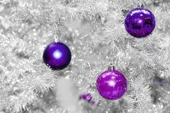 Безделушки покрашенного ультрамодного фиолетовые или ультрафиолетов на серебряной искусственной рождественской елке Стоковые Фотографии RF