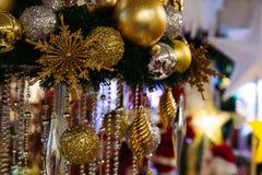 Безделушки рождества вися с освещением играют главные роли на заднем плане Стоковая Фотография