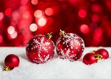 Безделушки рождества на красной предпосылке с sparkles Стоковое Фото