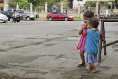 Бездомные дети мальчик и девушка ` s попрошайки, идя, позаботятся о один другого на дворе церков Стоковая Фотография RF