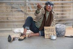 Бездомные старшие взрослые усаживание и умолять человека стоковое фото rf