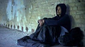 Бездомный беженец сидя в ворот, подготавливая к ночному в спальном мешке стоковое изображение