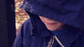 Бездомный подросток в куртке с голубым клобуком понизил его голову, мальчик ждет решение Помогите стоковые фотографии rf