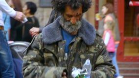 Бездомный пожилой человек смотрит через мусорный бак на занятой улице города, старике попрошайки ища еда в мусорном ящике видеоматериал